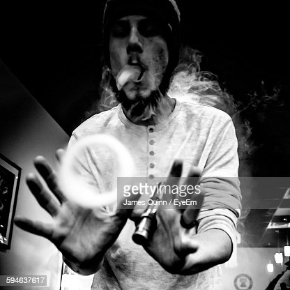 Low Angle View Of Young Man Making Smoke Ring Using Electronic Cigarette In Restaurant : Stock Photo