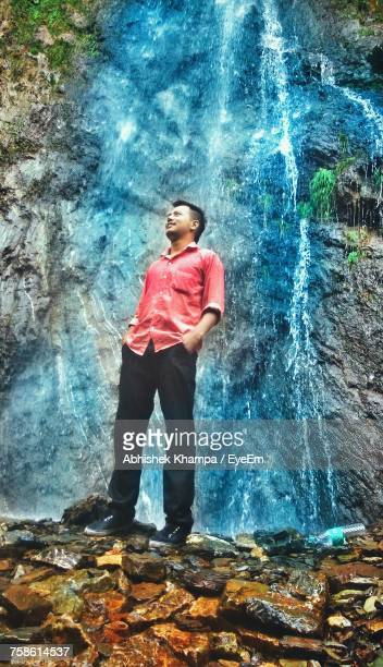 Low Angle View Of Young Man Standing Against Waterfall