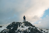 Low Angle View Of Young Woman Standing On Mountain Peak During Winter