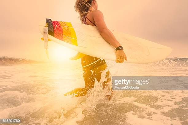Low Angle Women Surfer Running Into The Ocean At Sunset