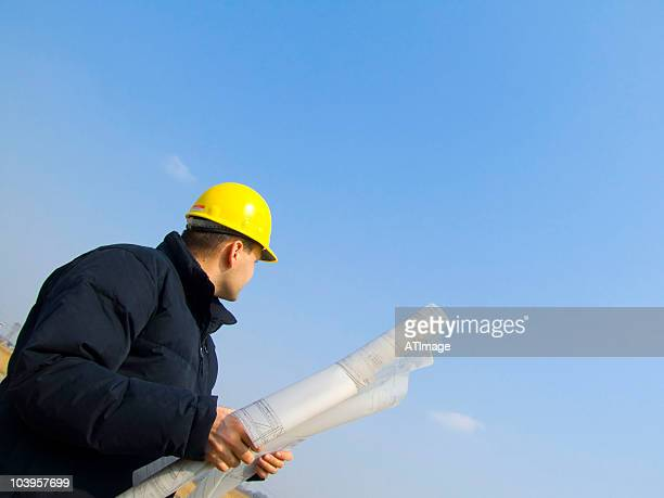 Low angled view of an engineer in a hard hat holding plans
