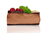 Lateral view of low carb no bake, sugar free, home made, raspberry chocolate cheesecake slice isolated on white with reflection