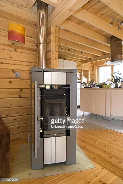 Low carbon central heating / water heating wood pellet burner in lounge of Finnishstyle energyefficient log house Hareslade Gower South Wales