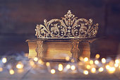 low key image of decorative crown on old book. vintage filtered with flitter overlay. selective focus.
