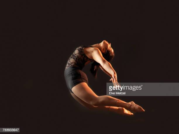 Low key shot of young female dancer bending backwards whilst leaping mid air