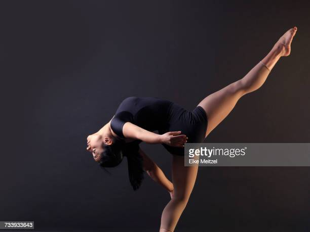 Low key shot of young female dancer bending backwards whilst standing on one leg