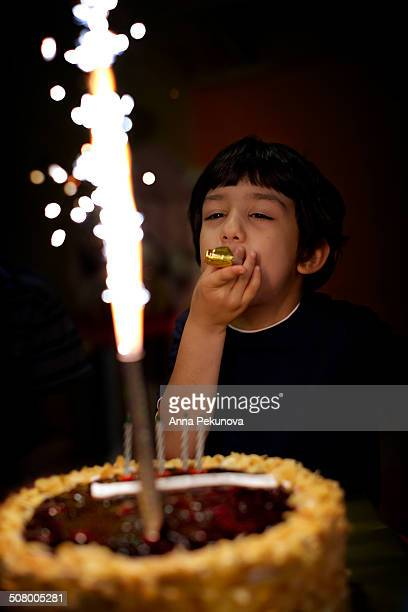 Low light portrait of boy behind birthday cake