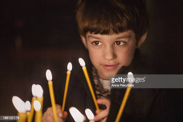 Low light portrait of boy lit with candles