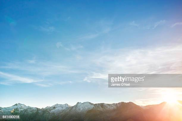 Low mountain range with expanse of sky and sun flare