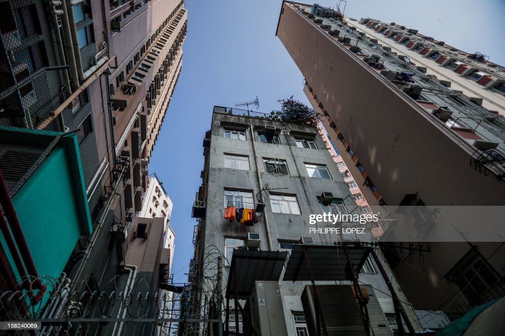 A low rise residential building is dwarfed by high rise buildings in Hong Kong on December 12, 2012. The International Monetary Fund warned that Hong Kong could see an abrupt fall in property prices after years of dramatic increases in one of the world's most expensive housing markets. AFP PHOTO / Philippe Lopez