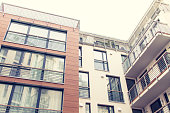 Low Angle Architectural Exterior View of Modern Low Rise Residential Condominium Building with Balconies and Large Windows with Bright Hazy Overcast Sky