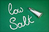 Salt shaker spelling out the words low salt on green background