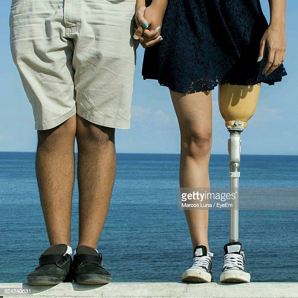 Low Section Handicapped Woman With Man Standing On Retaining Wall Against Sea