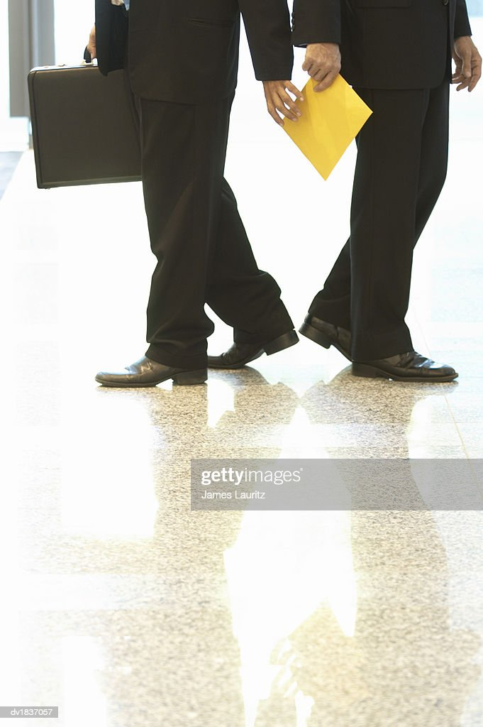 Low Section of a Businessman Handing an Envelope To Another Businessman : Foto de stock