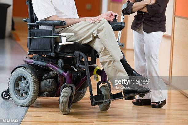 Low section of a handicapped man in a wheelchair and woman standing with cane.