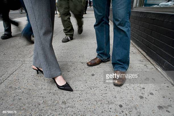 Low section of a man and a woman standing on a sidewalk, New York City