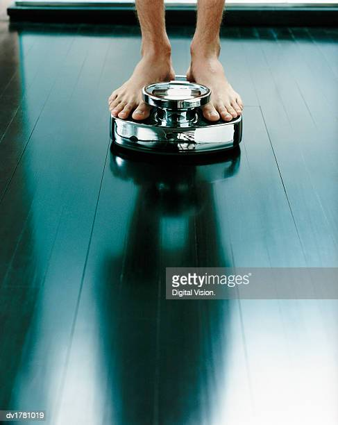 Low Section of a Man Standing on a Pair of Scales and His Shadow on the Polished Floor