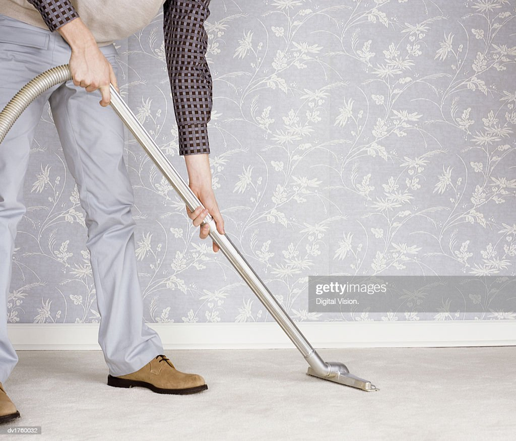 Low Section of a Man Using a Vacuum Cleaner : Stock Photo