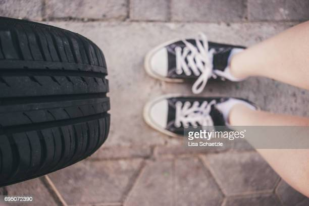 Low section of a woman changing tires.