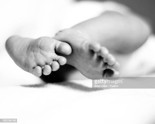 Low Section Of Baby Lying On Bed
