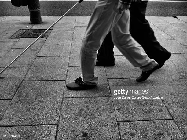Low Section Of Blind Man Walking With Person
