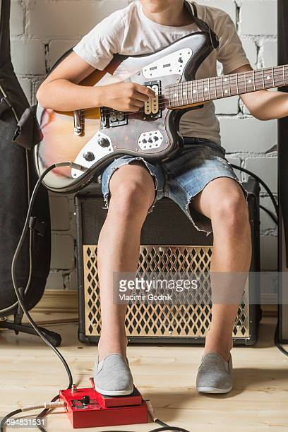 Low section of boy playing guitar at home