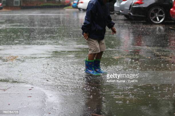 Low Section Of Boy Standing In Puddle Collected On Road
