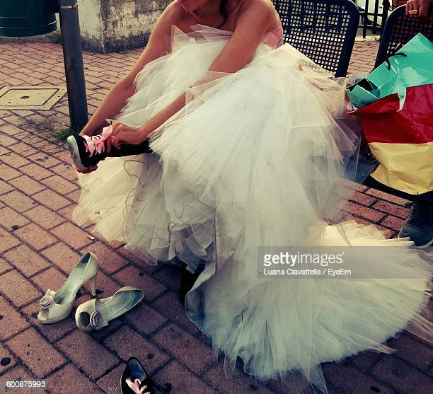 Low Section Of Bride Wearing Shoe While Sitting At Bus Stop