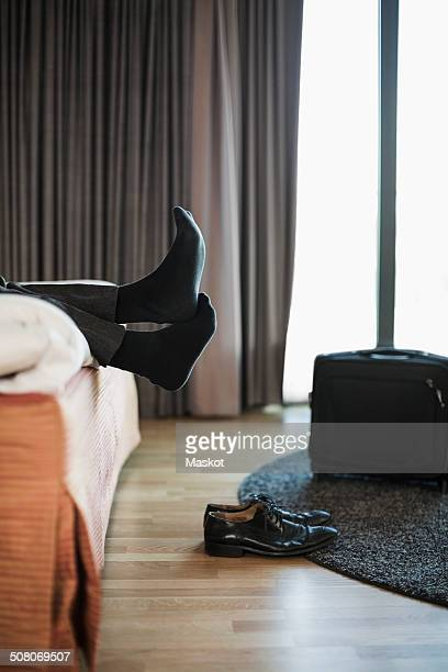 Low section of businessman relaxing on bed in hotel room