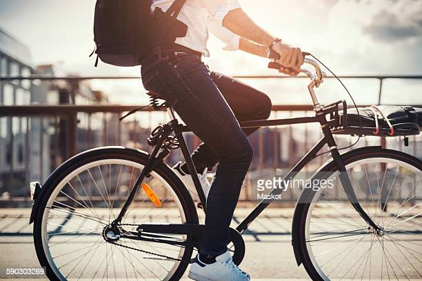 Low section of businessman riding bicycle on bridge