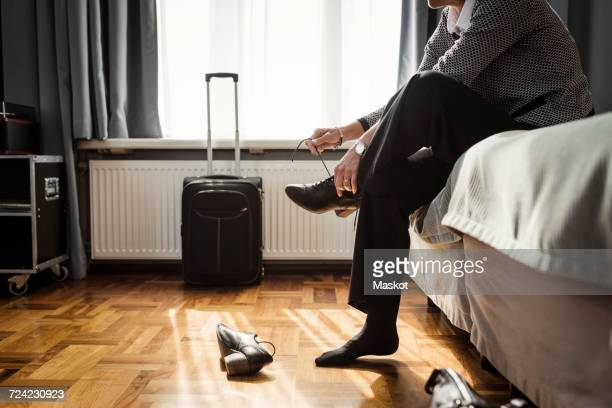 Low section of businesswoman tying shoelace sitting on bed at hotel room