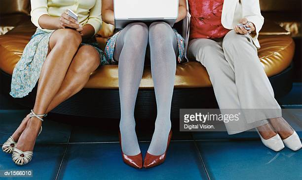Low Section of Businesswomen Sitting With a Calculator, Laptop Computer, and Mobile Phone