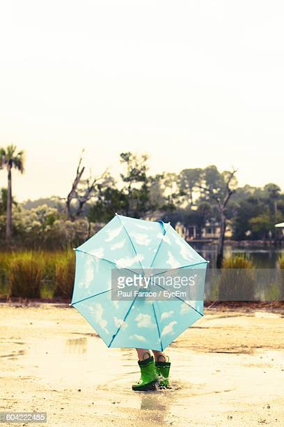 Low Section Of Child With Umbrella On Wet Field Against Sky During Rainy Season