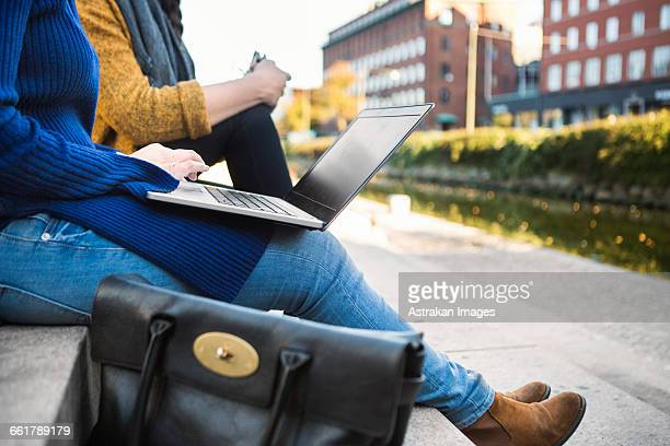 Low section of colleagues sitting on steps and using laptop