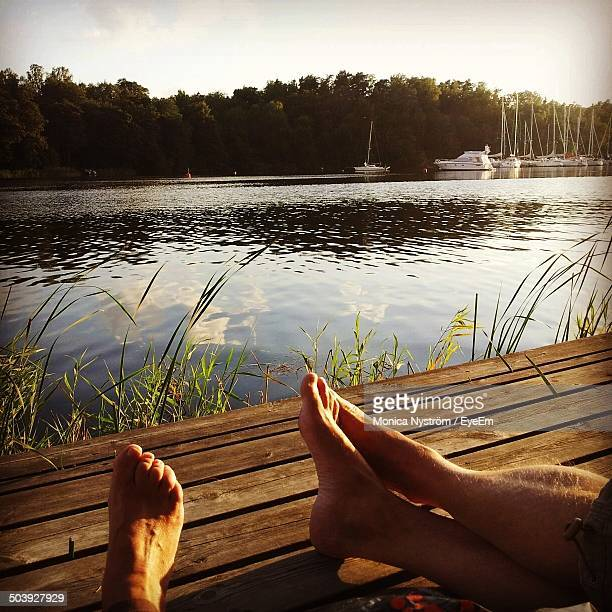 Low section of couple relaxing against calm lake