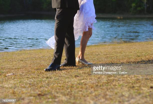 Low Section Of Couple Standing On Field
