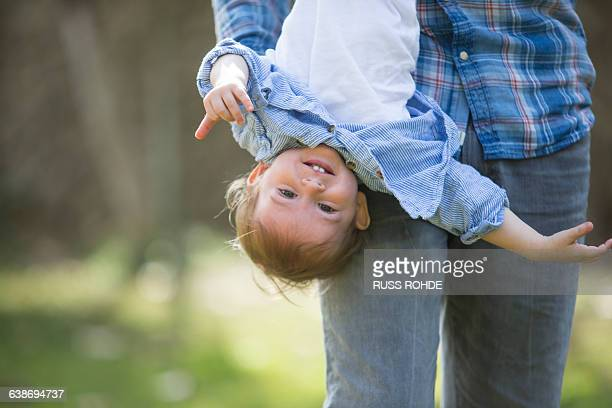 Low section of father hanging smiling baby boy upside down