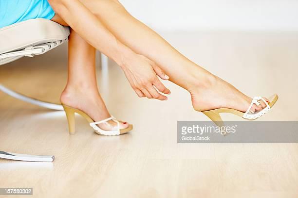 Parte inferior do sexo feminino tentar em novos sapatos de salto alto