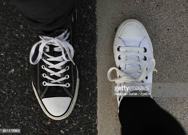 Low Section Of Friends Wearing Canvas Shoes On Road