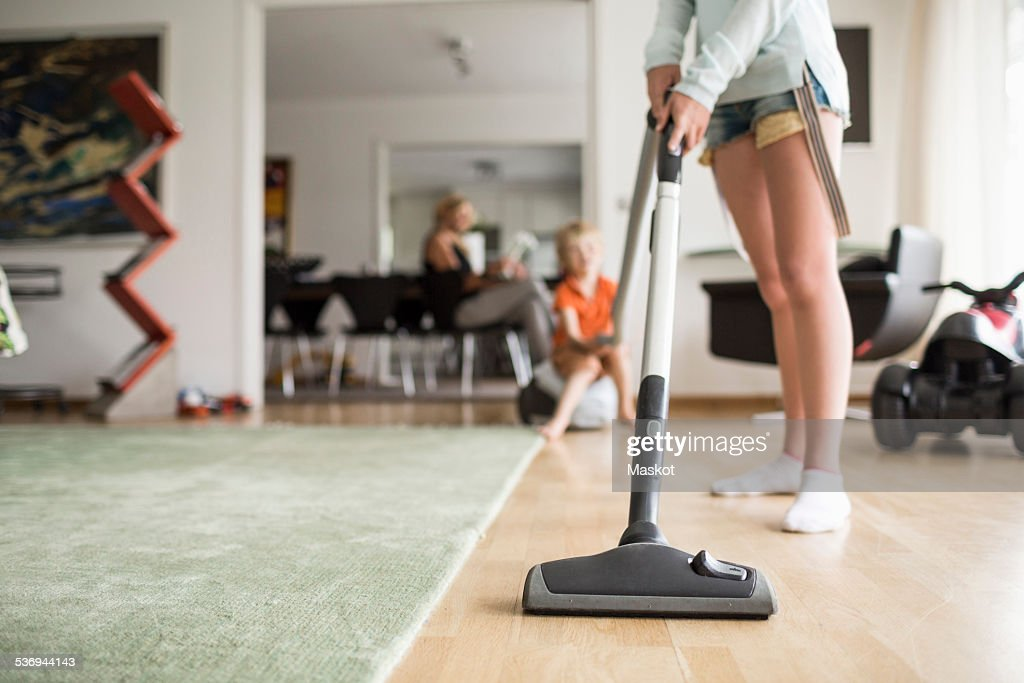 Low section of girl cleaning floor with vacuum cleaner at home
