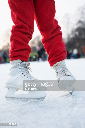 Low section of girl ice skating on rink