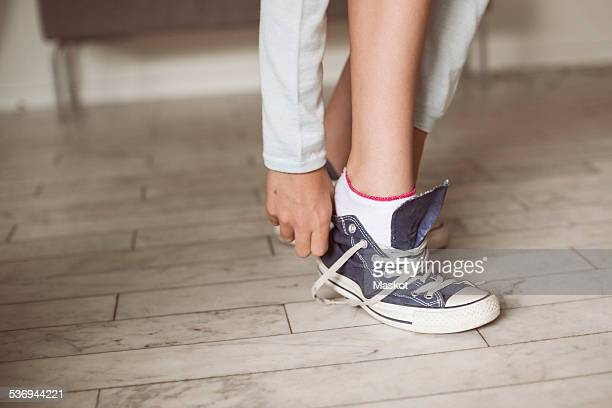 Low section of girl putting on canvas shoe at home