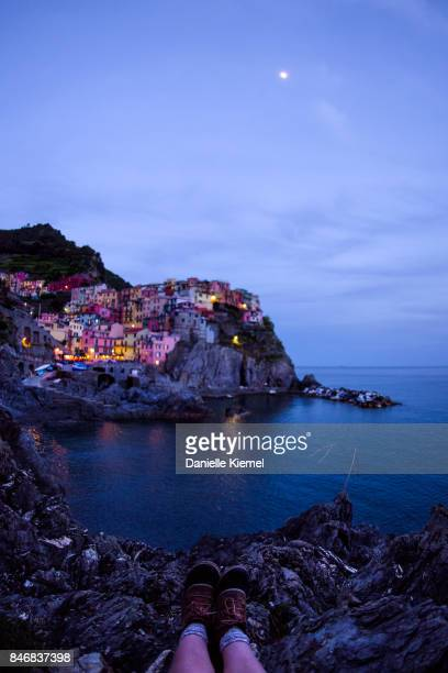 Low section of girl sitting on cliff, view of Manarola, Cinque Terre