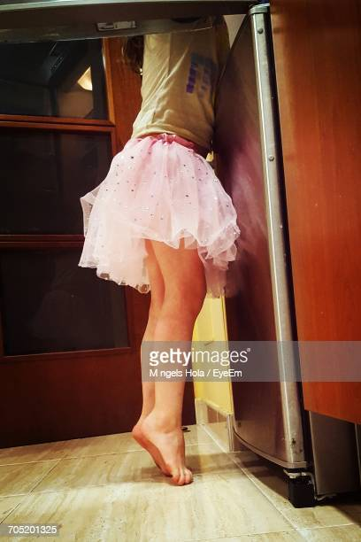 Low Section Of Girl Standing On Tiptoes In Kitchen