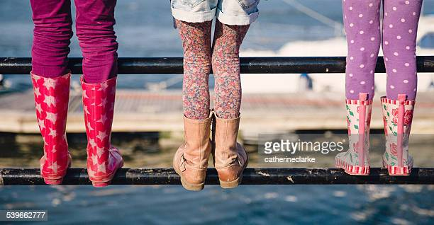 UK, Low section of girls (6-7, 8-9, 10-11) standing on railing