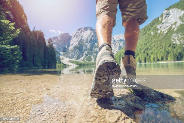 Low section of hiker at mountain lake, Dolomites, Italy