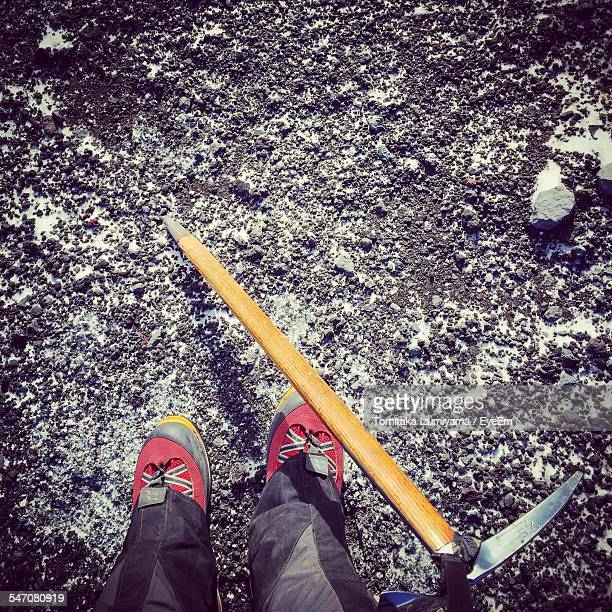 Low Section Of Hiker Standing By Ice Axe On Field