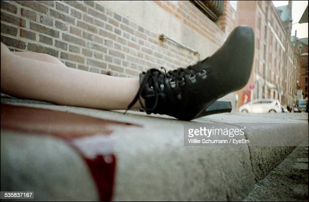 Low Section Of Injured Woman Lying On Sidewalk