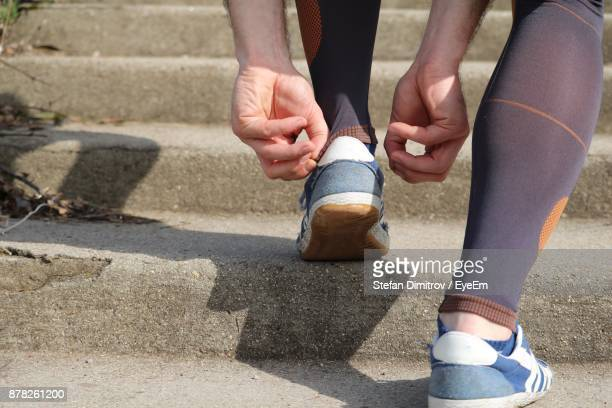 Low Section Of Man Adjusting Shoes On Steps