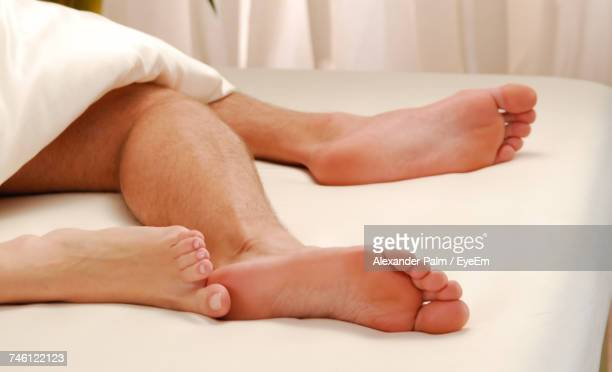 Low Section Of Man And Woman Lying On Bed